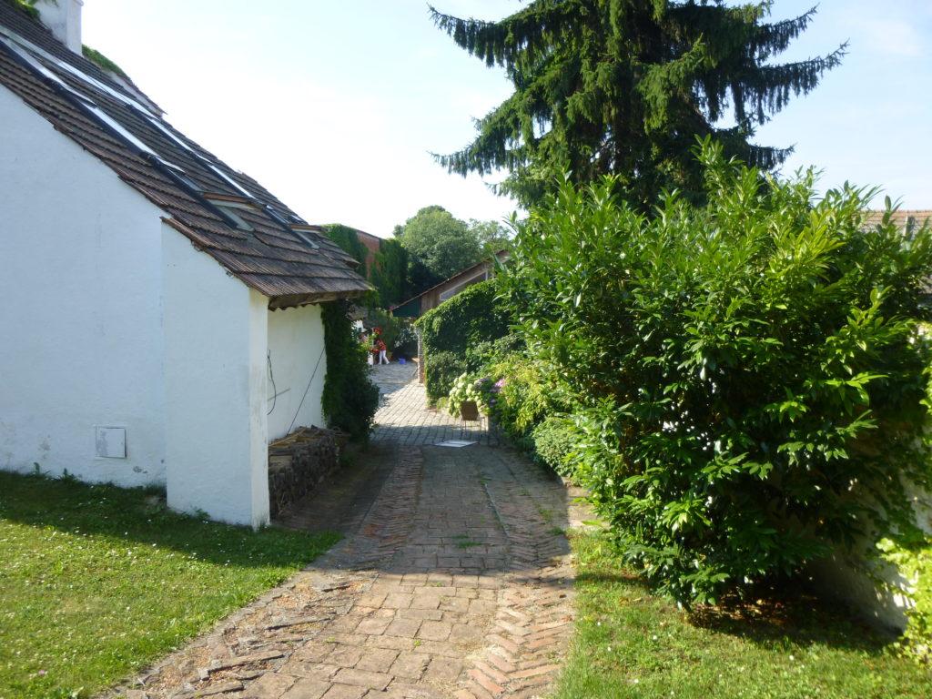 Pflasterstein Weg bergab im Innenhof des Biohofs zwischen Haus und grünen Büschen.