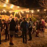 Innenhof am Biohof geschmückt mit Stroh, Lichterketten, Besucher mit Glühwein am Abend.